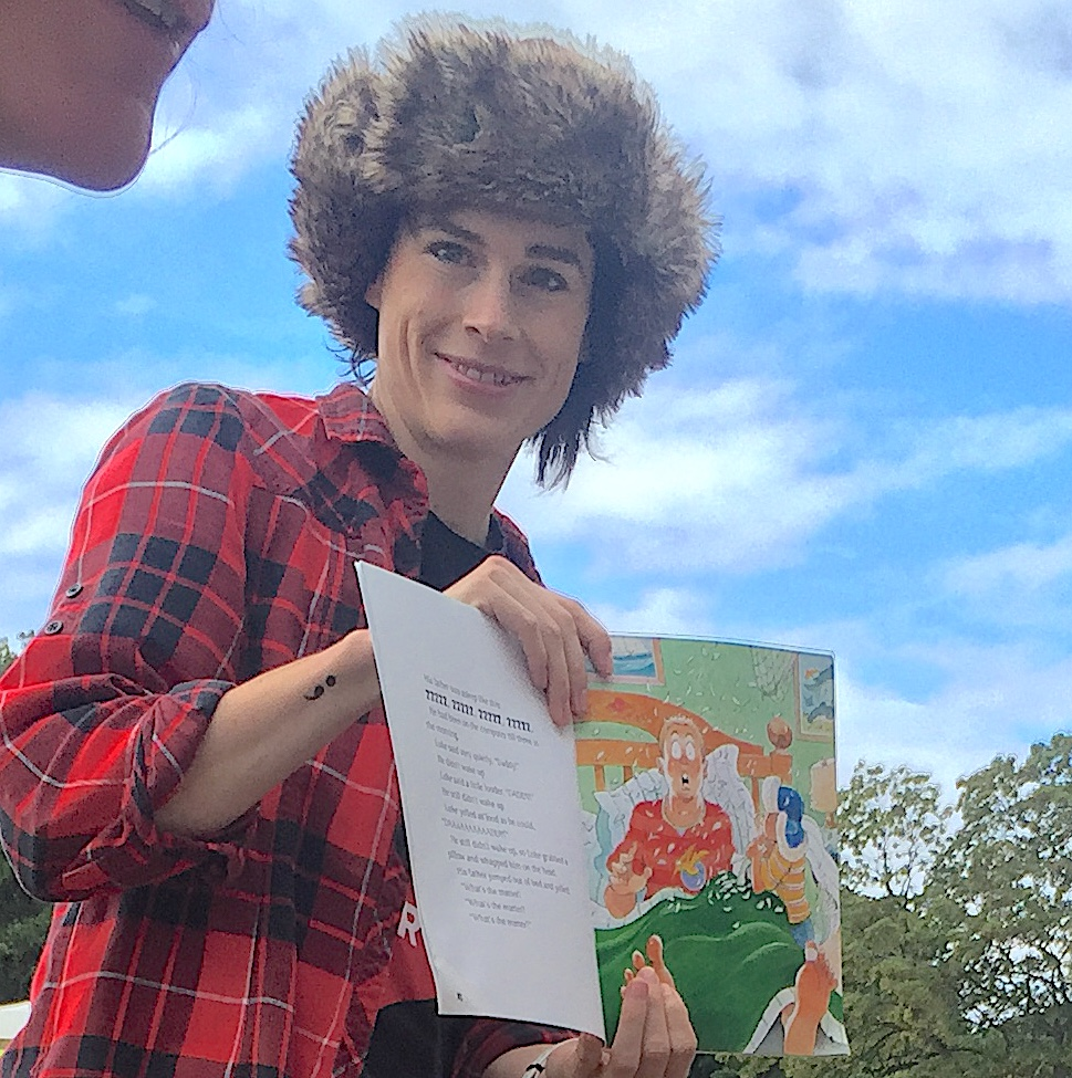 "Rachel Hahn wears a faux fur hat and plaid shirt while she reads ""Moose!"" by Robert Munsch in the park outside the Malmö city library."